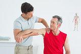 Physiotherapist massaging mature mans arm