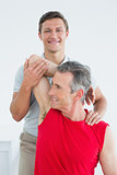 Physiotherapist stretching a mature mans arm