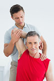 Physiotherapist stretching a smiling mature mans arm