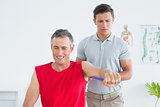 Physiotherapist examining a smiling mature mans arm