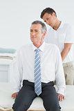 Chiropractor examining mature man