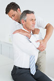<ale chiropractor examining mature man