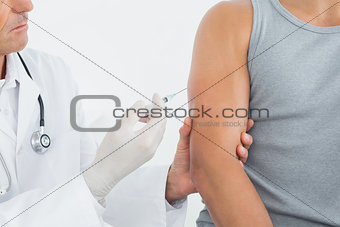Cid section of a male doctor injecting a patients arm