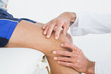 Close-up of hands examining patients knee