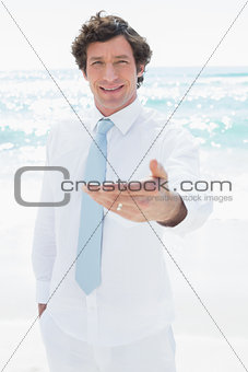 Handsome groom smiling and offering his hand