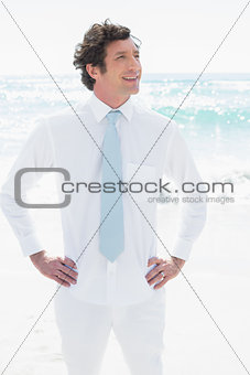 Handsome groom smiling with hands on hips