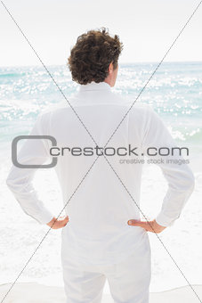 Handsome groom looking out to sea with hands on hips