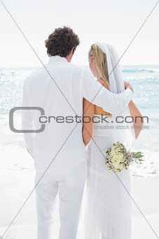 Bride and groom looking out to sea embracing