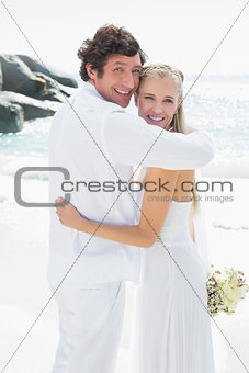 Smiling bride and groom looking at camera hugging