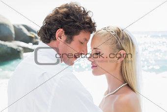 Smiling bride and groom embracing each other