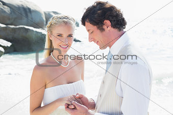 Pretty bride smiling at camera with husband