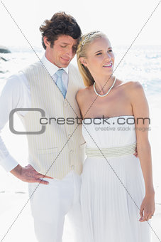 Attractive bride and groom embracing and looking away