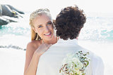 Pretty blonde bride smiling at camera while hugging husband