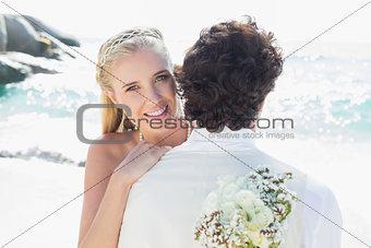 Pretty blonde bride smiling at camera while hugging husband