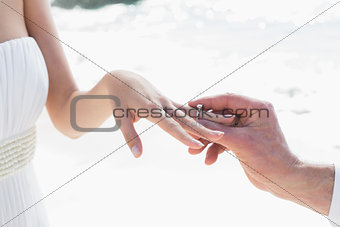 Man placing ring on brides finger
