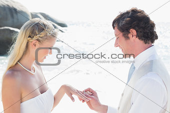 Man placing ring on happy brides finger