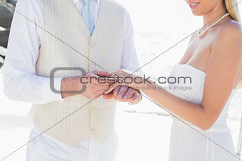 Man placing ring on smiling brides finger