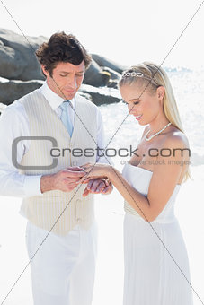 Man placing ring on smiling blonde brides finger