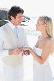 Handsome man putting ring on smiling blonde brides finger