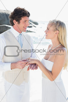 Handsome man putting ring on smiling blonde brides finger