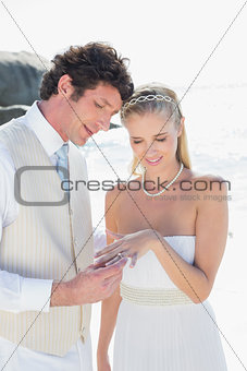Handsome man placing ring on smiling blonde brides finger