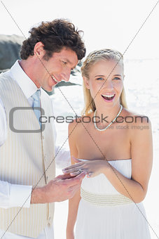 Handsome man placing ring on smiling brides finger