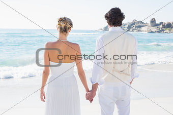 Bride and groom holding hands looking out to sea