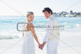 Bride and groom holding hands looking at camera