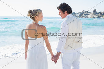 Bride and groom holding hands looking at each other