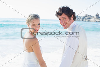 Bride and groom holding hands smiling at the camera