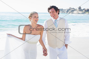 Newlyweds walking hand in hand and laughing