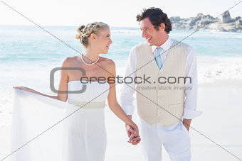 Newlyweds walking hand in hand and smiling at each other