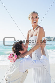 Laughing groom picking up his pretty blonde wife smiling at camera