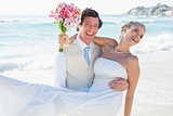 Laughing groom carrying his pretty blonde wife smiling at camera