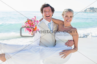 Groom carrying his pretty blonde wife smiling at camera