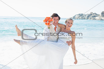 Handsome groom carrying his pretty blonde wife