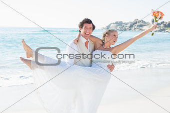 Handsome groom carrying his beautiful new wife
