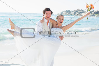 Handsome groom carrying his beautiful wife