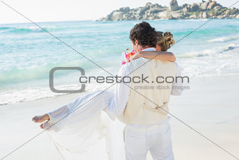 Handsome groom carrying his beautiful wife out to the water