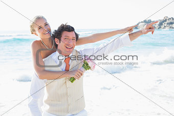 Newlyweds pointing to something smiling at camera