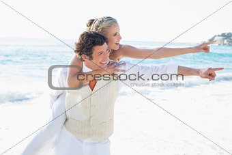 Newlyweds pointing to something and smiling