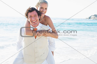 Blonde bride getting a piggy back from new husband