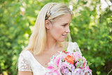 Blonde bride holding big bouquet