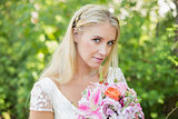 Blonde bride holding big bouquet smiling at camera
