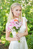Blonde bride holding bouquet smiling at camera