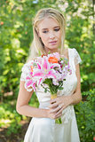 Blonde smiling bride holding bouquet