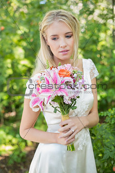 Blonde smiling bride holding bouquet