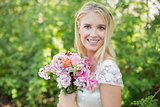 Blonde smiling bride holding bouquet looking at camera