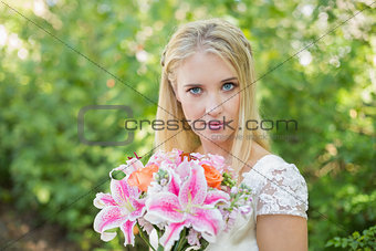Blonde bride holding colourful bouquet looking at camera