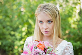 Blonde bride holding colourful bouquet looking away